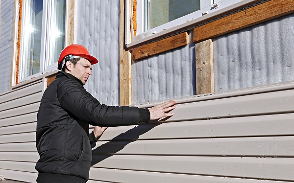Installing cladding on the side of a house.
