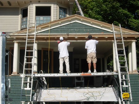 Builders applying house cladding.